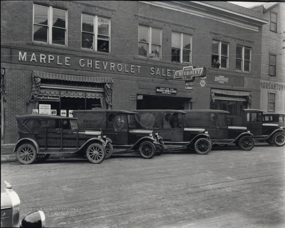 Exterior of Marple Chevrolet Dealership; trucks and automobiles are parked in front; located on corner of University Avenue and Walnut Street.<br />