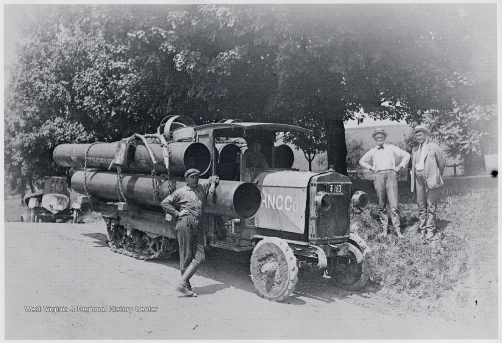 Men standing beside a halftrack carrying oil equipment.