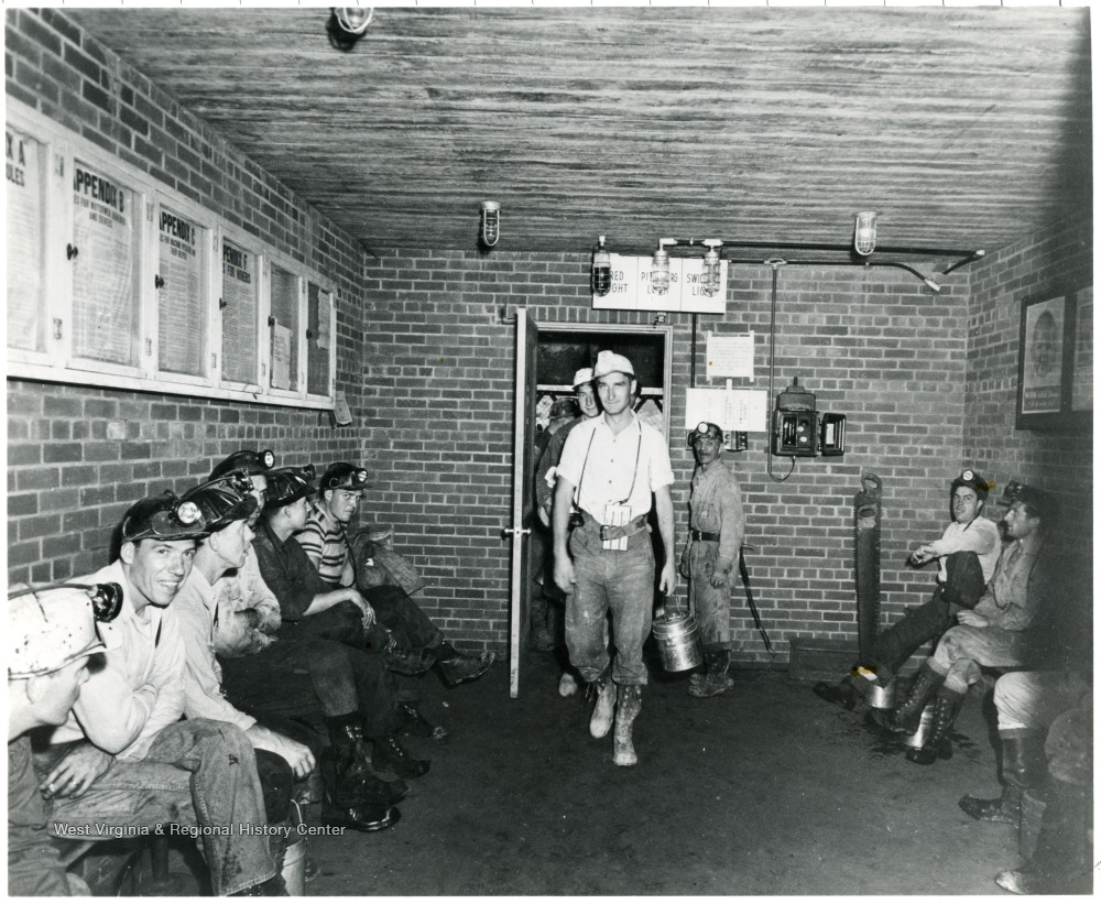 Miners entering a room with other miners sitting on benches lining the walls during a Consolidation Coal Co. Inspection trip.