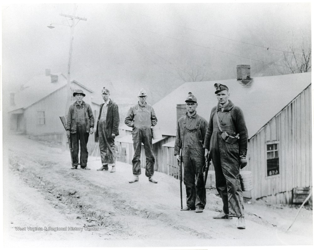 Five miners with guns and buckets stop on the road in front of houses for a picture.