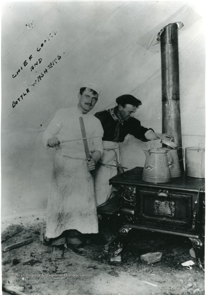Two men cook on a stove in a tent.