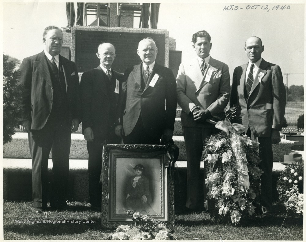 Group portrait of five men with standing in front of the Mother Jones Memorial.  A framed portrait of Mother Jones sits on the ground in front of the group.