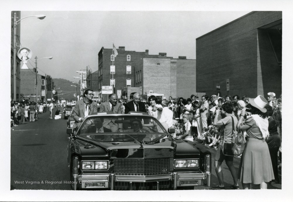 Jay Rockefller, an unidentified man, and Joe Dimaggio are riding in a car during a parade in the 1st Annual Italian Heritage Festival, Clarksburg, West Virginia. Tim Cotter (pointing)is standing next to the car.