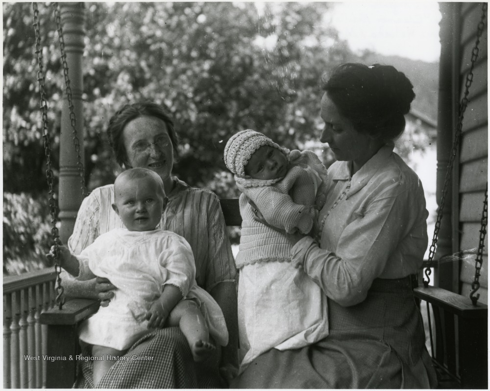 Olga Aegerter and another woman sitting on a porch swing while holding two babies.
