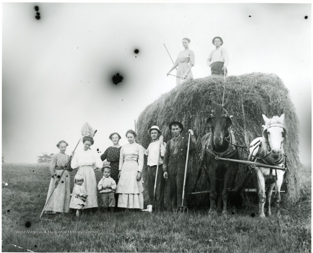 The Aegerter Family standing beside two horses pulling a large bale of hay.  Helvetia, W. Va.