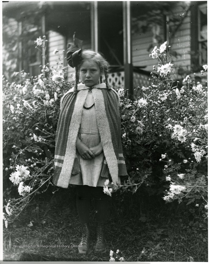 Grace Holtkamp (Herrstrom) standing in the middle of flowers.  House in the background.  Helvetia, W. Va.