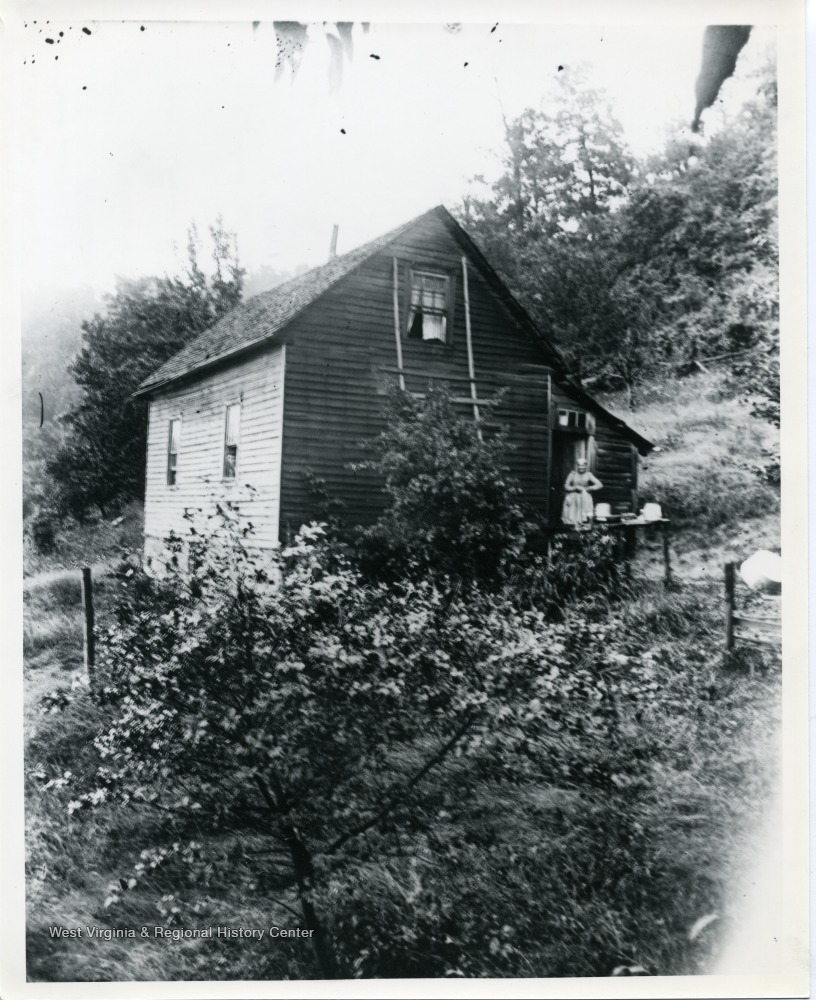 An unidentified woman standing on a porch in Helvetia, West Virginia. The wooden two-story house is surrounded by trees.