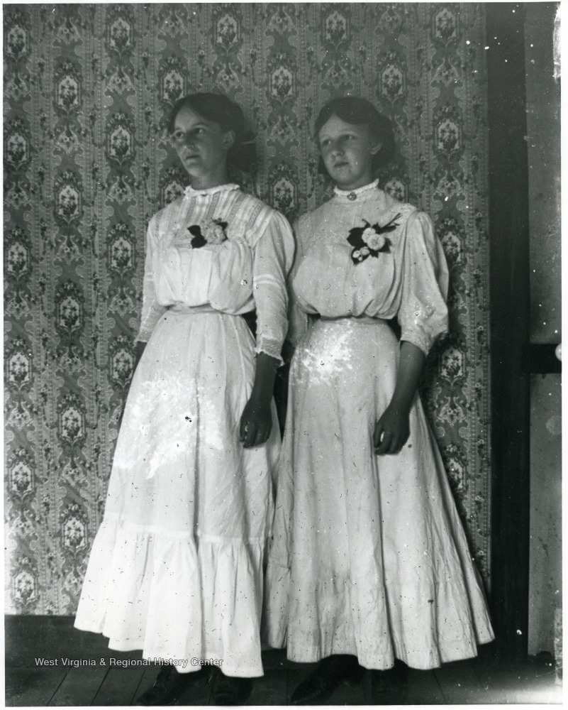Two women standing together in front of wallpapered background.  Helvetia, W. Va.