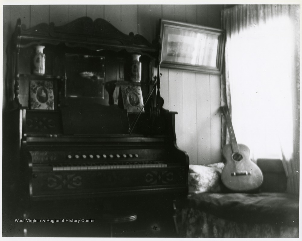 Interior view of a Helvetia home - a guitar leaning on a couch, a bow and violin resting top of a pump organ.