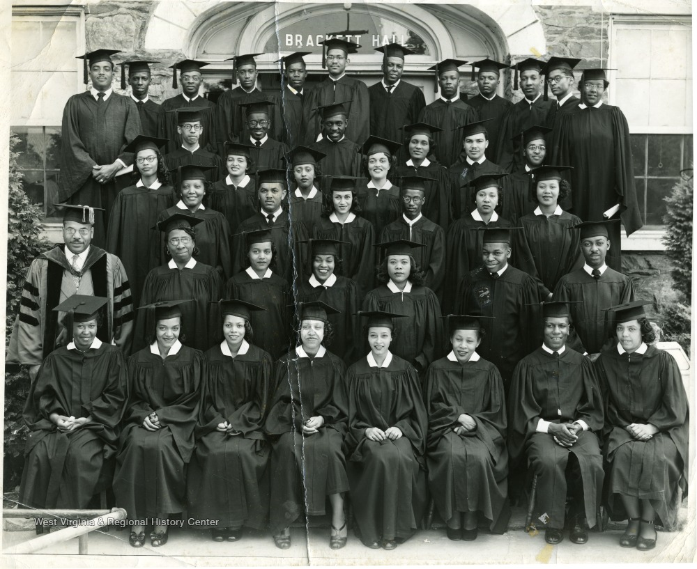 Graduates from Stover College standing on the stairs of Brackett Hall.