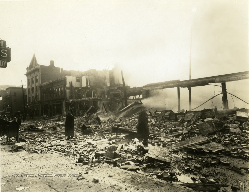 'Strand Theatre fire on High Street in Morgantown', W. Va. Debris from theatre can be seen on street. People standing throughout the debris. Damage from fire seen throughout structures.