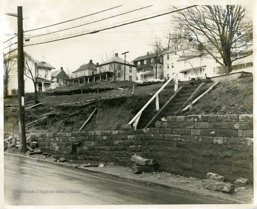 A view of a broken wall and partial sidewalk along University Avenue at Sunnyside in Morgantown, West Virginia.