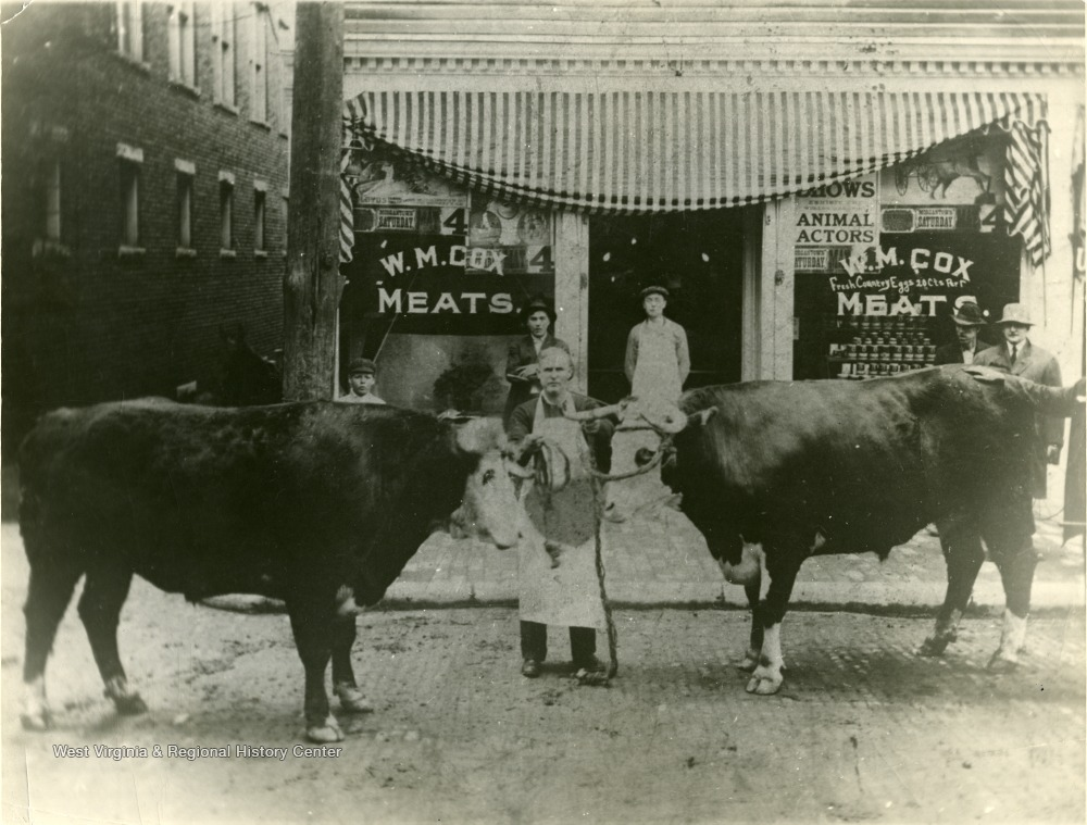 Man standing with two steer in front of the W. M. Cox Meat Market on the northwest corner of Chancery Row and Chestnut Street.