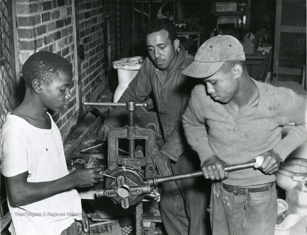 A scene of three African American boys putting some equipment into a vice at the West Virginia Industrial School for Colored Boys.