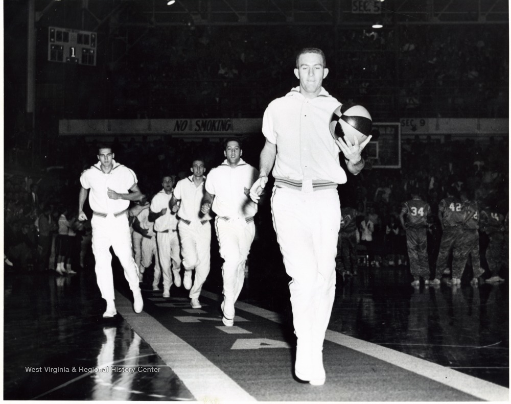 Willie Akers leads the team down the carpet and Jerry West is on the left. The carpet is rolled out before each home game for the WVU team to enter on to the court. This is one of the best traditions in NCAA basketball.