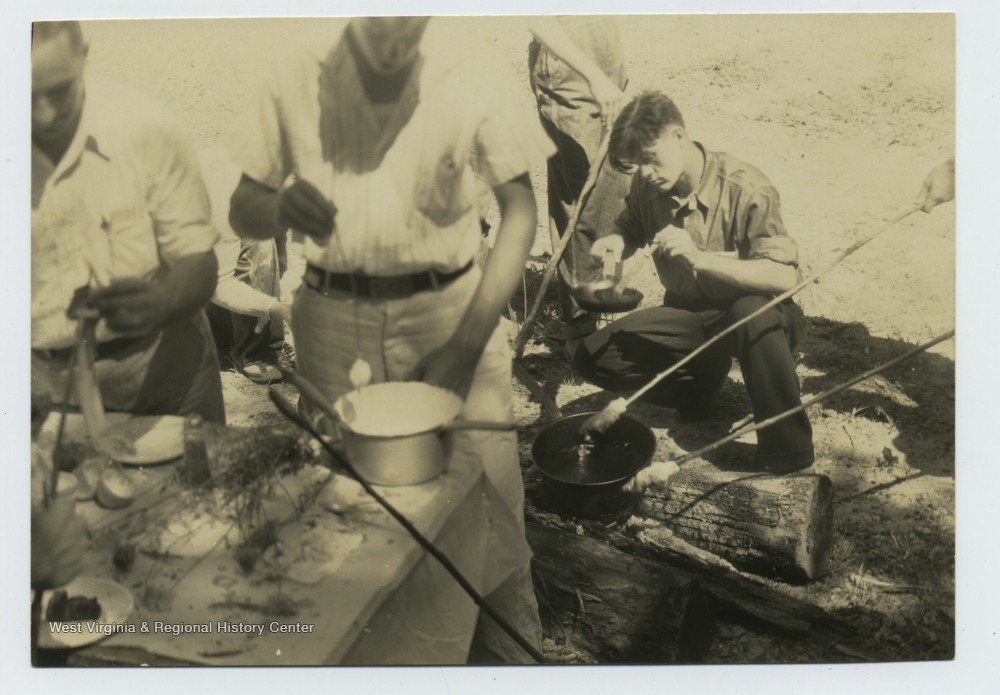 Boys appear to be cooking on sticks and in a pan over a fire.