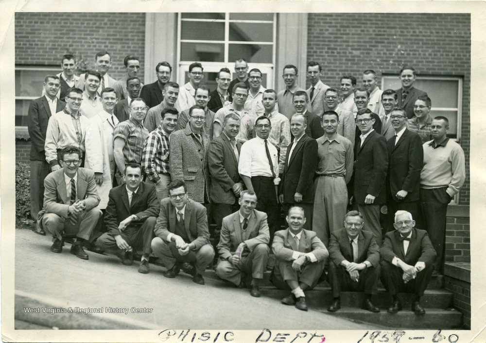 A group portrait of the graduate students and instructors of the WVU Physics Department.  The graduate students are standing and the instructors are kneeling.   Instructors (left to right) are: Gerald Arthur, Michael Pavlovic, Arnold Levine, Douglas Williamson, Harvey Rexrode, Charles Thomas, Dr. Ford.