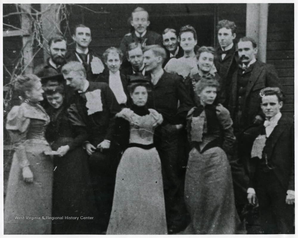 "'Corn bread breakfast at ""The modest brown cottage,"" A.B. Fleming's home in Charleston, W. Va. While Governor, center back; Walton Miller; 2nd row: Alec Quarrier, George McClintic, Mary Long, George Summers, Brad Clarkson, Minnie Owings (married Clarence Watson), Gypsy Fleming, Bob Ewing, Harrison B. Smith; Front Row: Ida Fleming, neice of Mrs. P.C. Gallaher, Fontaine Brown, Miss Caldwell, Bess Summers, Jim Ewing'"