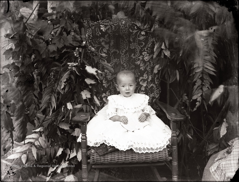 A portrait of child in a wicker chair against foliage, Helvetia, W. Va.
