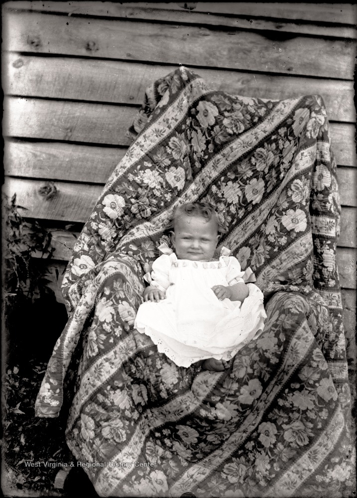 A portrait of infant in a draped chair taken outside.