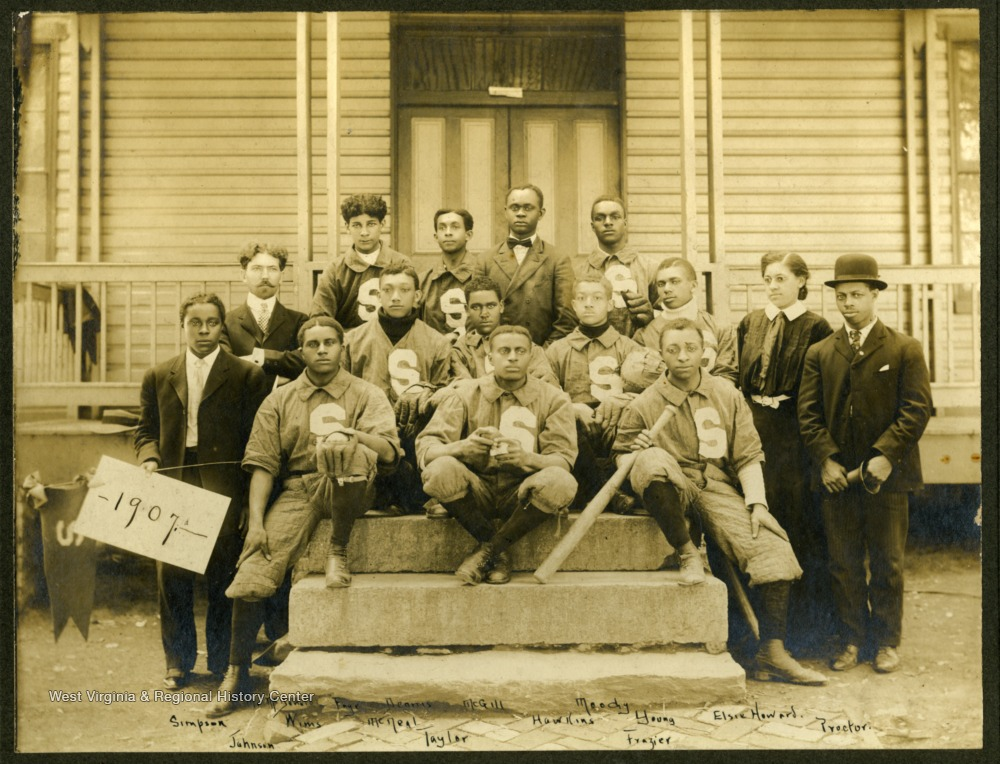1907 Storer College baseball team sitting on the steps of a building. First Row: Mr. McDonald, Paige, Dennis, McGill, Moody. Second Row: Simpson, Wims, McNeal, Hakins, Young, Elsie Howard. Third Row: Johnson, Taylor, Frazier, Proctor.