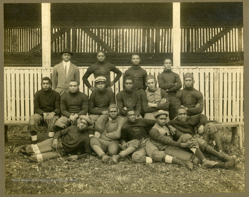 Storer College football team in uniform in front of dugouts.