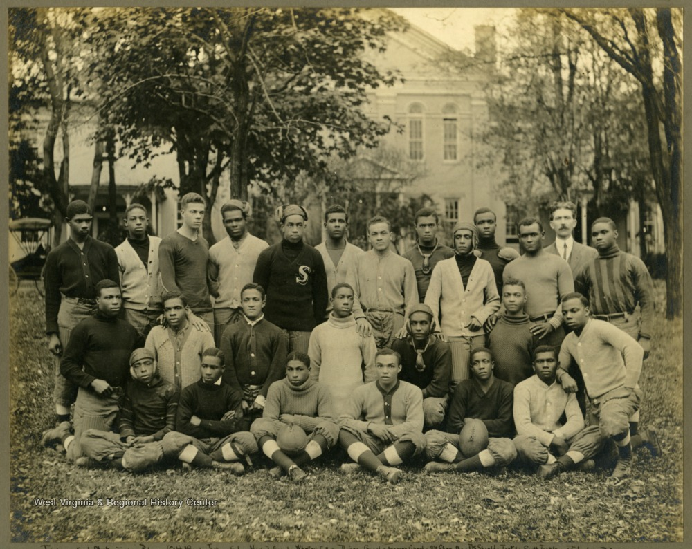 Group photo of Storer College football team, partially in uniform. Back Row: Fisher(END), Motley(TACKLE), Palmer(CAPT/GUARD), Jackson(END), Howard(GUARD), Wheaton(FB), Diggs(GUARD), Frazier(GUARD), McGhee(QB), DeShields(TACKLE), Scott(TACKLE), Ridgley(FB). Middle Row: Thomas(Center), Hopewell(TACKLE), Williamson(QB), Mackel(HB), Green(HB), Brimagt(HB). Front Row: Camper(END), Winders(QB), White(CENTER), Parks(GUARD), Crawford(END), Freeman(GUARD).