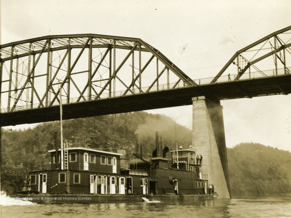"The ship ""Dwight F. Davis"" sails under a bridge. This ship was built by The Charles Ward Engineering Works in Charleston, West Virginia."