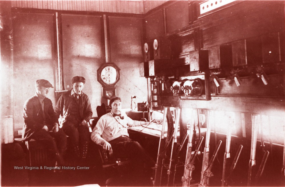Harry Simpson is seated at the desk with the telegraph transmitter and two unidentified men are sitting behind him. The telegraph office was located at the Chesapeake and  Ohio Depot in Prince, Fayette County, West Virginia.