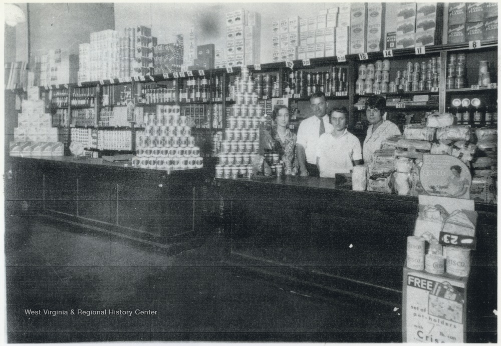 Inside the store located on the corner of 3rd Avenue, between Ballengee and Temple streets. Employees behind the counter are identified, from left to right, as Lorene Jones, an unidentified man, Mary Eades, and Maycle Scott who is the mother of Jack Scott.