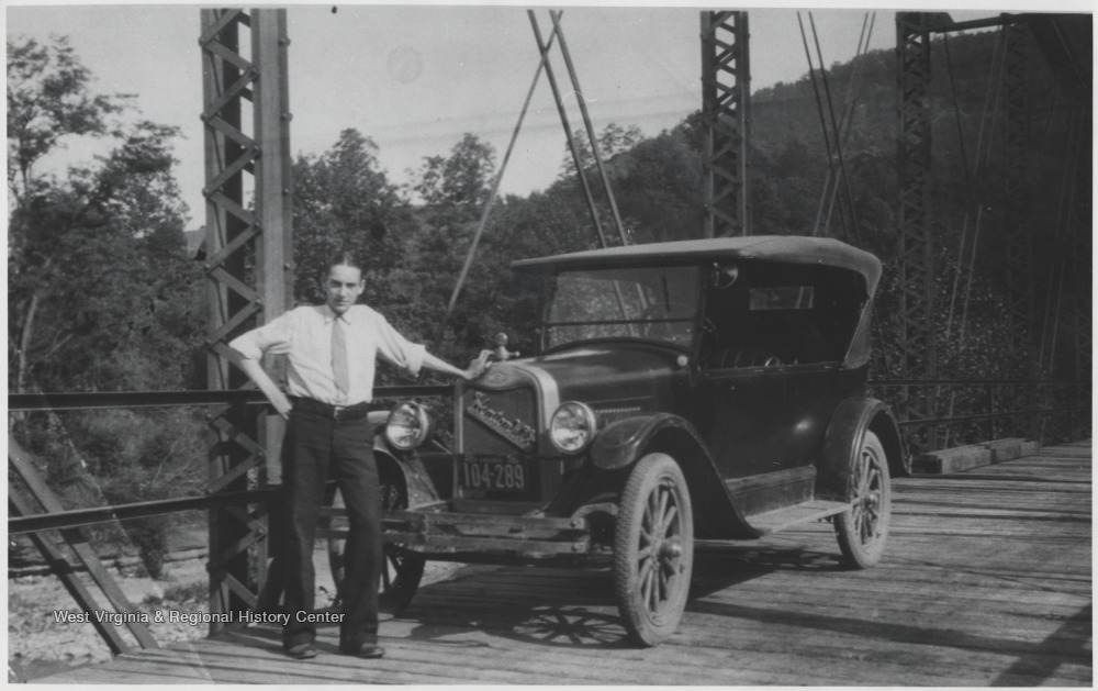 The unidentified man poses beside a car on top of the newly completed bridge over the mouth of the Bluestone River.