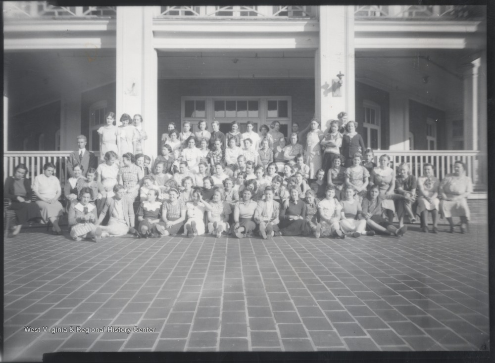 Female students and their teachers are pictured in front of the building. Subjects unidentified.