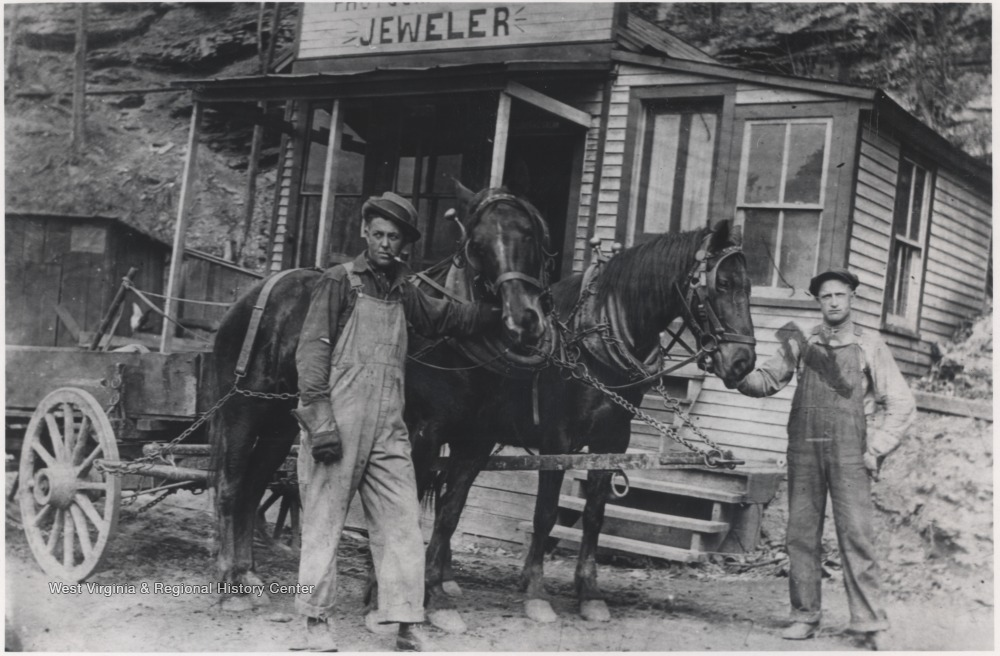 The two men are pictured outside of the store located in Happy Hollow with two horses pulling a wagon.