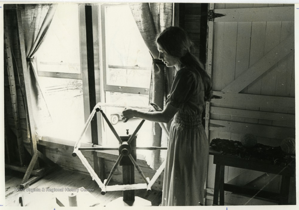 Mary Beth Lind spins at a spinning wheel on the second floor of the Old Mill crafts shop in Harman, West Virginia.The photos in this collection were used in chapters that appeared in Mountain Trace, a publication of Parkersburg High School in West Virginia, edited by Kenneth G. Gilbert.