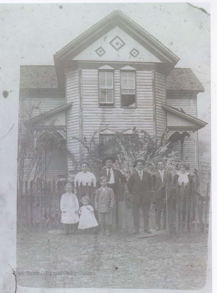 A family of unidentified persons poses in front of the home of Jack Warhop, pitcher for the New York Yankees.