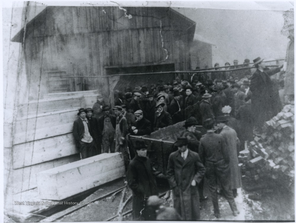 A group of men inspect the damage caused by an explosion at the mine. Subjects unidentified.