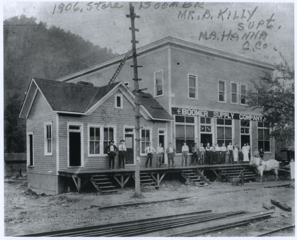 A group of men and boys are lined up on the store's porch. Mr. B. Killy is identified as the superintendent.