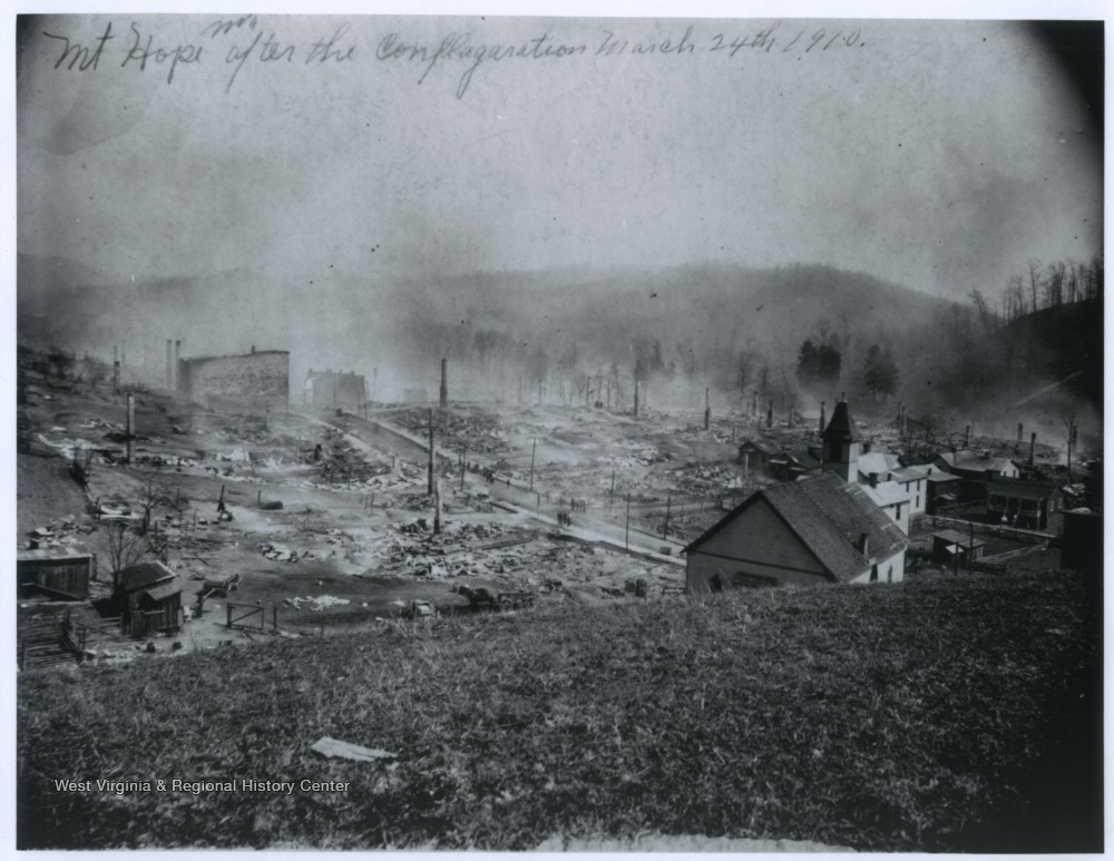 """Mt Hope W. Va. after the conflagration March 24th, 1910""  The majority of the buildings in town have been destroyed.  A number of brick chimneys are left standing after the wooden buildings burned."