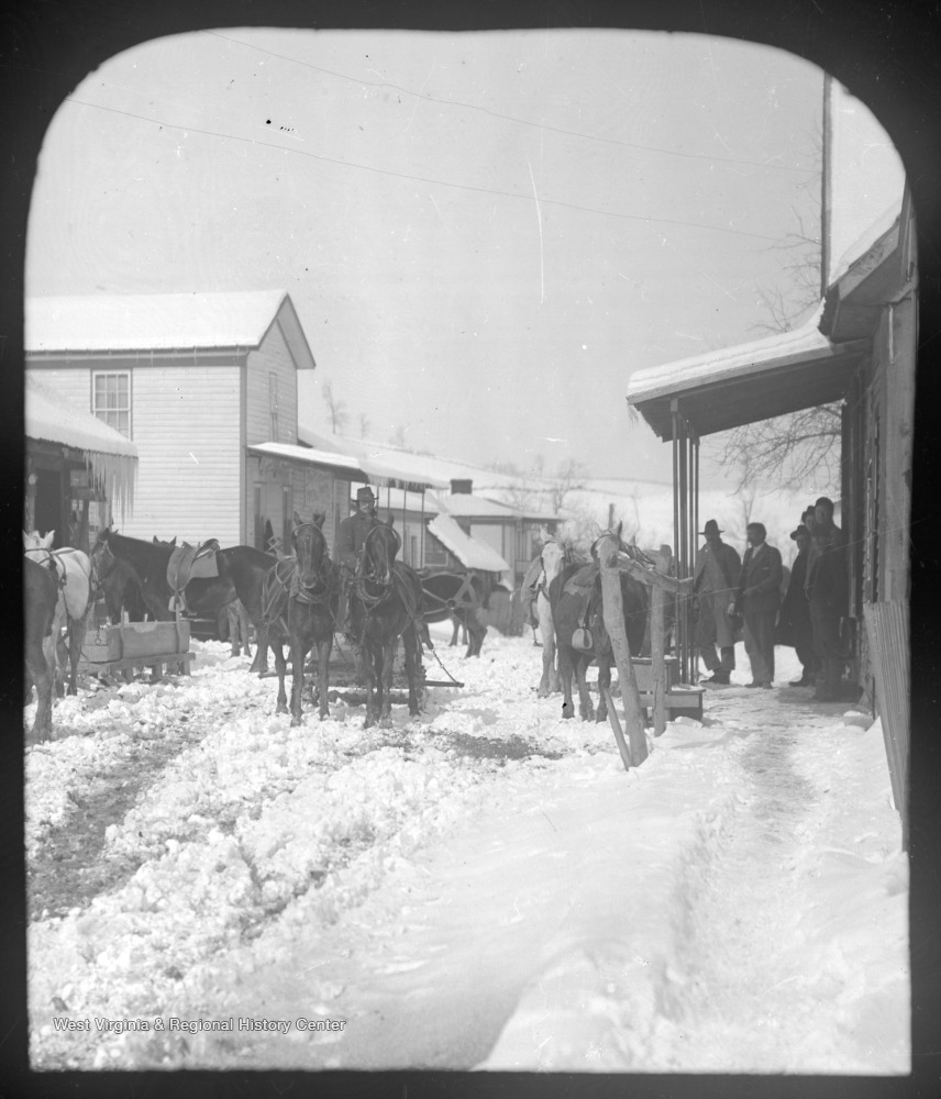 View of the snow-covered street which is filled with horse-drawn carriages. A group of men stand beneath an awning on the right.