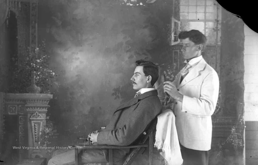 A man sits while a barber combs and styles his hair.