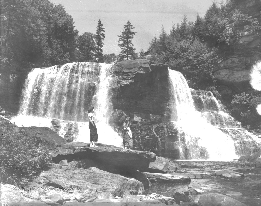 A woman stands on a rock as she observe the scenery. In the background is a waterfall.