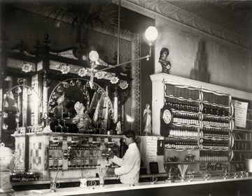 Interior of drug store (probably Ream's Drug Store) with soda fountain on 304 High Street, Morgantown; the counterman is Harry Selby.
