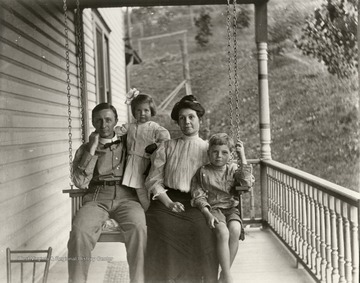 Family of four sitting on a porch swing, Morgantown.<br />