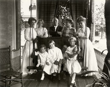Portrait of family on a porch; adults are standing and children are sitting on a porch swing.