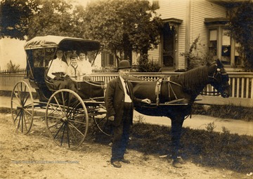 Group portrait of McKean Family with their horse and carriage prior to participating in a parade in Beckley.  From left to right:  Gertie (Beasley) McKean, son Clay, daughter Mae, and Sam McKean.