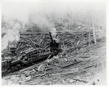 Crane loading logs on flatbed train car.  Workers securing logs.