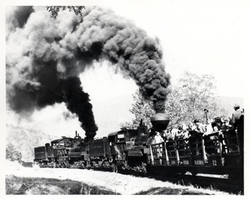 Shay Locomotives No. 1 and 4 pushing people in a cart up a hill. Cass, W.V.
