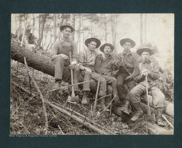Five men sit on a fallen tree.  John Swisher is seated in the middle.  The man seated on the far right, on the lower end of the fallen tree, is possibly William Vernon Riley.  The man seated second from the far right, and second from the end of the lower part of the fallen tree, is possibly William Vernon Riley's brother, Harry Vincent Riley.
