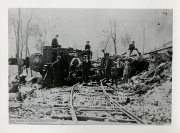 Men standing in front and on top of train wreckage.