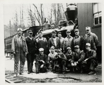 Group portrait of men standing in front of a train.